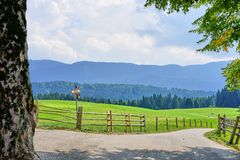 Idyllic view over farmers fields in Bavaria to the Mountains beyond. Bavarian Countryside with quiet lane, farmers fields and distant misty mountains stock photography