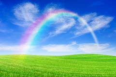 Idyllic view, rainbow over green field. Idyllic landscape, rainbow over rolling green fields, in the background blue sky and white clouds stock images