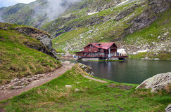 Idyllic view with typical lodge on Balea Lake shore in Fagaras M Stock Photography