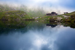 Idyllic view with typical lodge on Balea Lake shore in Fagaras M Royalty Free Stock Photos