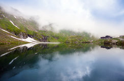 Idyllic view with typical lodge on Balea Lake shore in Fagaras M Stock Photos