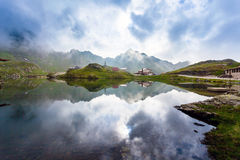 Idyllic view with typical lodges on Balea Lake shore in Fagaras Royalty Free Stock Image