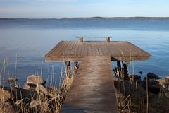 Idyllic View Of The Wooden Pier. With Simple Bench On The Lake stock photo