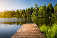 Idyllic view of the wooden pier in the lake with mountain scenery background. Alps in the early morning Stock Photos