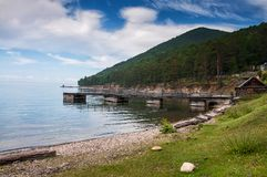 Idyllic view of the wooden pier in the lake with mountain scenery background. Lake Baikal in the day. Idyllic view of the wooden pier in the lake with mountain Stock Photo