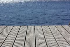 Idyllic view of the wooden pier in the lake or river mooring surface reflecting mirror sky.  stock photos