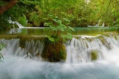Idyllic waterfall. Landscape with beautiful green lake and cascading waterfalls Royalty Free Stock Photography