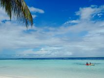 Idyllic white beach with palm trees and people kayaking. In shallow water Stock Photo