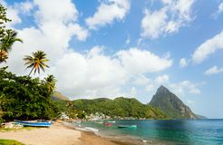 Idyllic beach at Caribbean. Idyllic white sand tropical beach with view to Piton mountains in Saint Lucia Caribbean royalty free stock photography