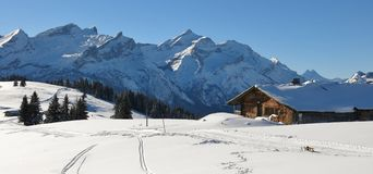 Old timber hut and snow covered mountain Range. Mountains Schlau. Idyllic winter landscape near Gstaad, Switzerland. Snow covered mountains Schlauchhorn and Royalty Free Stock Photography