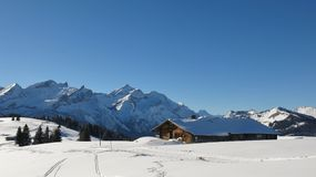 Idyllic winter landscape near Gstaad, Switzerland. Snow covered. Old timber hut and snow covered mountain Range. Mountains Schlauchhorn and Oldenhorn Stock Photography
