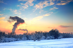 Idyllic winter landscape spoiled by factory smoke Royalty Free Stock Images