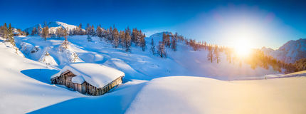 Idyllic winter mountain landscape in the Alps at sunset. Panoramic view of beautiful winter mountain landscape with snow capped mountain cabin in the Alps in stock photos