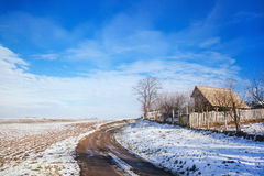 Idyllic winter scene with house and snow covered fields Stock Images