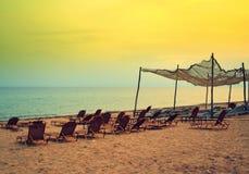 Idyllic yellow beach lounges fishnet Stock Photography