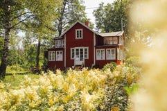 Idyllically beläget typisk rött svenskt landshus arkivfoto