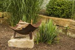 Idylliczna graba z metalu pożarniczym pucharem w ogródzie z orname fotografia royalty free