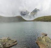Idylliczny halny jezioro z mgła udźwigiem wyjawiać wysokie wysokogórskie góry obraz stock