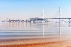 Idylliczny seascape w Świątobliwym Petersburg, Rosja z podwyższoną autostradą, odległym mostem i odbiciami, obrazy stock