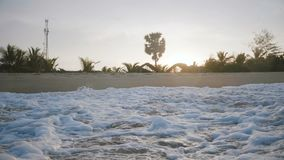 Idylliczny w górę tło strzału foamy białe ocean fale bryzga przy egzotyczną zmierzch plażą z zadziwiającymi drzewkami palmowymi zbiory