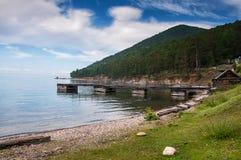 Idylliczny widok drewniany molo w jeziorze z halnym scenerii tłem Jeziorny Baikal w dniu zdjęcie stock