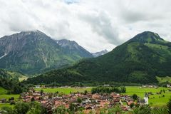 Idyllisch berglandschap met een klein dorp en bergen op de achtergrond royalty-vrije stock afbeelding