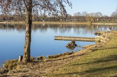 Idyllisch meer met vrije tijdsfaciliteiten en recreatief gebied in de lente met aangrenzende toewijzingen stock afbeeldingen