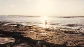 Idyllische Ansicht der jungen durchdachten Frau im Hut, der auf Strand szenische Ansicht des Meerblicks während des erstaunlichen stock video footage