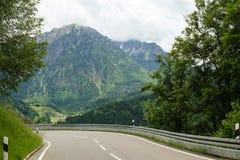 Idyllische Berglandschaft mit einer Straße in der Front und Bergen im Hintergrund stockbilder