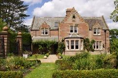 Idyllische buitenhuis en tuinen royalty-vrije stock afbeelding