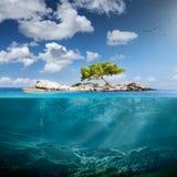 Idyllische kleine Insel mit einzigem Baum im Ozean lizenzfreie stockfotos