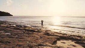 Idyllische Luftbrummenansicht der jungen durchdachten Frau im Hut, der auf Strand szenische Ansicht des Meerblicks während aufpas stock video