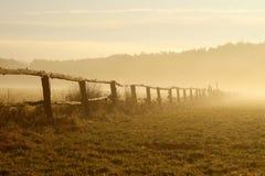 Idyllischer Zaun auf einem nebelhaften Feld am Sonnenaufgang Lizenzfreies Stockfoto