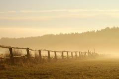 Idyllischer Zaun auf einem nebelhaften Feld am Sonnenaufgang Lizenzfreies Stockbild