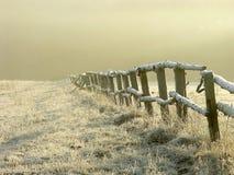 Idyllischer Zaun auf einem nebelhaften Feld am Sonnenaufgang Lizenzfreie Stockbilder
