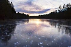 Idyllisk och iskall sjö i solnedgång Arkivfoton
