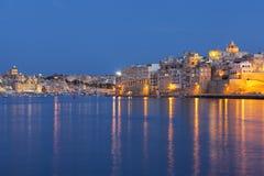 Idyllisk sikt av Malta Tricity område med ljus som glöder i havet Arkivbilder