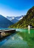 Idyllisk sjö med fjällängarna Arkivbild