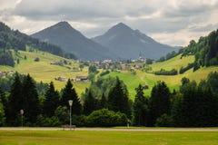 Idylliskt berglandskap med en liten by och berg i bakgrunden royaltyfria foton