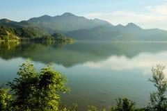 Idylliskt dimmigt berglandskap med en sjö och berg i bakgrunden fotografering för bildbyråer