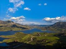 Idylliskt landskap av en sjö under bergskedja mot cloudscape arkivbild