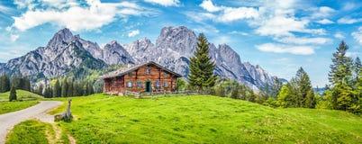 Idylliskt landskap i fjällängarna med bergchalet Royaltyfri Foto