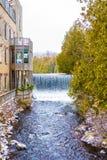 Idylliskt naturligt landskap, vattenfall av en flod nära byggnad med balkonger royaltyfri fotografi