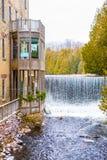Idylliskt naturligt landskap, vattenfall av en flod nära byggnad med balkonger royaltyfria bilder