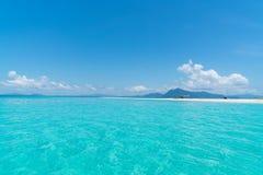 Idylliskt tropiskt hav, sandstång och avlägsna berg royaltyfri bild