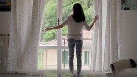 idzie spaceru kobiety potomstwa Dziewczyna komesi okno i otwierają zasłony Dziewczyna ocenia pogodę outside zdjęcie wideo
