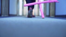 Iemand die clown-vormige schoenen dragen loopt in gang draggin groot roze kruis stock footage