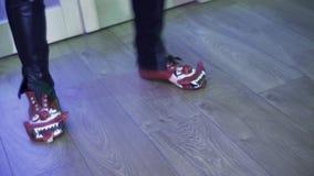 Iemand die clown-vormige schoenen en donkere broek dragen danst vreugdevol in ruimte stock video