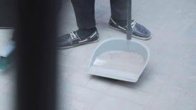 Iemand die tennisschoenen dragen veegt weg puin van witte vloer in blik stock video