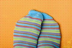 Iemand die zijn of haar voeten wrijven die kleurrijke sokken dragen Stock Foto's